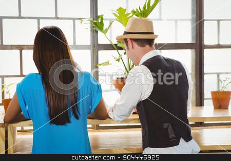 Cute couple sitting inside a cafe stock photo, Cute couple sitting inside a cafe on a sunny day by Wavebreak Media