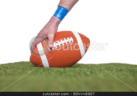 American football player placing the ball stock photo, American football player placing the ball on the grass over a white background by Wavebreak Media