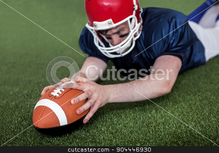 American football player scoring a touchdown stock photo, Determined american football player scoring a touchdown on the field by Wavebreak Media