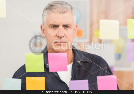 Casual businessman looking at a post it wall stock photo, Casual businessman looking at a post it wall at office by Wavebreak Media