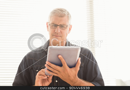Attentive businessman scrolling on his tablet stock photo, Attentive businessman scrolling on his tablet at the office by Wavebreak Media
