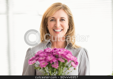 Smiling casual businesswoman holding flowers stock photo, Portrait of smiling casual businesswoman holding flowers in the office by Wavebreak Media