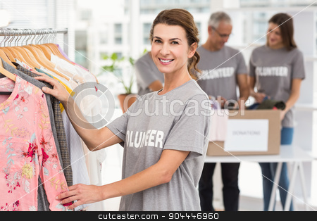 Smiling female volunteer choosing clothes stock photo, Portrait of smiling female volunteer choosing clothes in the office by Wavebreak Media