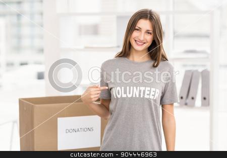 Smiling brunette volunteer showing her shirt stock photo, Portrait of smiling brunette volunteer showing her shirt in the office by Wavebreak Media