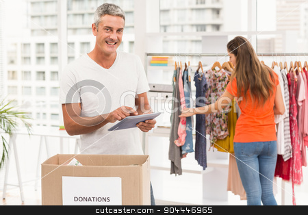 Casual businessman with donation box and tablet stock photo, Portrait of casual businessman with donation box and tablet in the office by Wavebreak Media