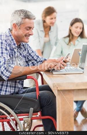 Casual businessman in wheelchair using smartphone stock photo, Casual businessman in wheelchair using smartphone in the office by Wavebreak Media