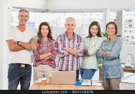 Casual business team smiling at camera with arms crossed stock photo, Casual business team smiling at camera with arms crossed in the office by Wavebreak Media