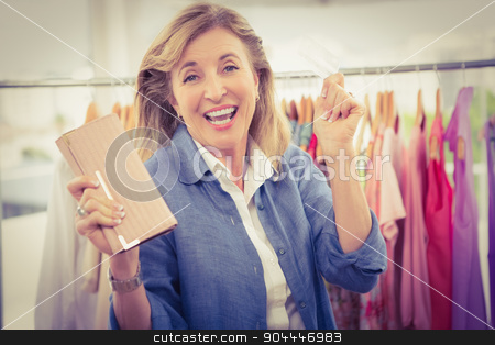 Cheering woman going shopping and showing wallet stock photo, Portrait of cheering woman going shopping and showing wallet in clothing store by Wavebreak Media