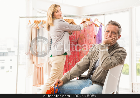 Bored man waiting for his shopping woman stock photo, Portrait of bored man waiting for his shopping woman in clothing store by Wavebreak Media