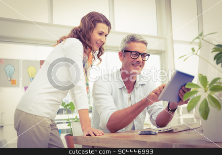Two smiling casual designers working with tablet stock photo, Two smiling casual designers working with tablet in the office by Wavebreak Media