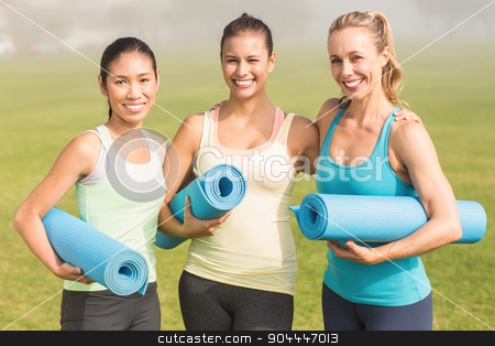 Smiling sporty women with exercise mats  stock photo, Portrait of smiling sporty women with exercise mats in parkland by Wavebreak Media