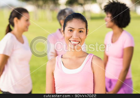 Smiling woman wearing pink for breast cancer in front of friends stock photo, Portrait of smiling woman wearing pink for breast cancer in front of friends by Wavebreak Media