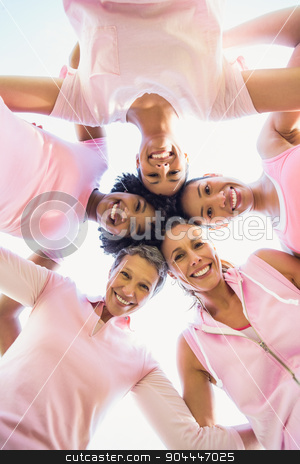 Women wearing pink for breast cancer with arms around stock photo, Women wearing pink for breast cancer with arms around in parkland by Wavebreak Media