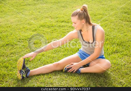 Smiling sporty blonde stretching legs stock photo, Smiling sporty blonde stretching legs in parkland by Wavebreak Media