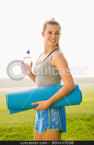 Sporty blonde holding exercise mat and water bottle stock photo, Sporty blonde holding exercise mat and water bottle in parkland by Wavebreak Media