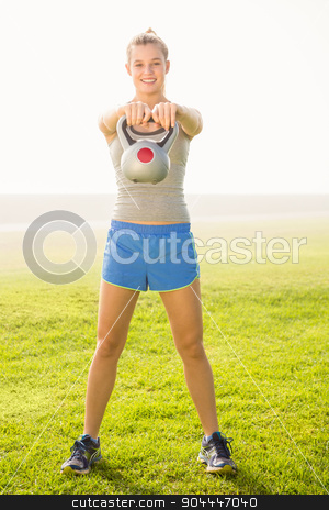 Smiling sporty blonde exercising with kettlebell  stock photo, Portrait of smiling sporty blonde exercising with kettlebell in parkland by Wavebreak Media