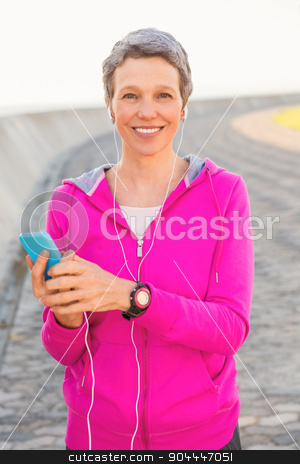 Smiling sporty woman enjoying music and holding phone stock photo, Portrait of smiling sporty woman enjoying music and holding phone at promenade by Wavebreak Media