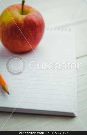 View of an apple and notepad stock photo, View of an apple and notepad lying on the desk by Wavebreak Media