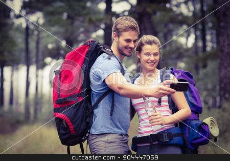 Young happy couple hiking in the nature stock photo, Young happy couple hiking in the nature and taking a selfie by Wavebreak Media