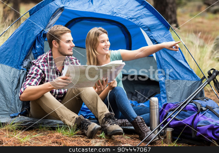 Young pretty hiker couple sitting in a tent pointing stock photo, Young pretty hiker couple sitting in a tent pointing in the nature by Wavebreak Media