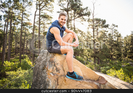 Young happy jogger sitting on rock and looking at camera stock photo, Young happy jogger sitting on rock and looking at camera in the nature by Wavebreak Media
