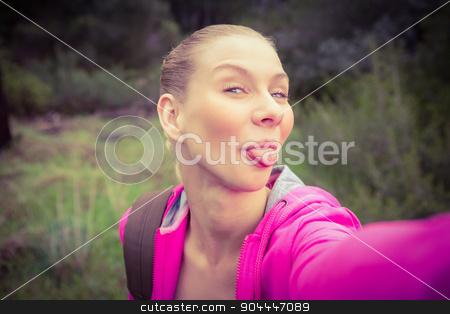 Smiling female hiker taking a funny selfie stock photo, Portrait of a smiling female hiker taking a funny selfie in the nature by Wavebreak Media