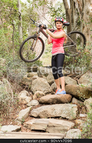 Blonde athlete carrying her mountain bike over rocks stock photo, Blonde athlete carrying her mountain bike over rocks in the nature by Wavebreak Media