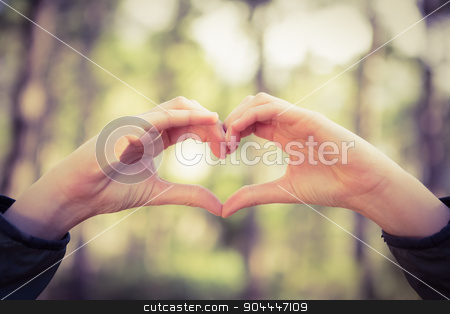 Carefree female hiker framing heart with hands stock photo, Carefree female hiker framing heart with hands in the nature by Wavebreak Media