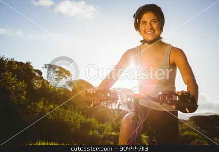 Smiling athletic brunette sitting on mountain bike stock photo, Smiling athletic brunette sitting on mountain bike in the nature by Wavebreak Media