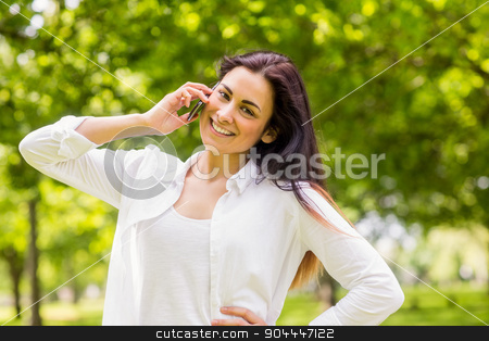 Beautiful brunette in the park making a call stock photo, Beautiful brunette in the park making a call on a sunny day by Wavebreak Media