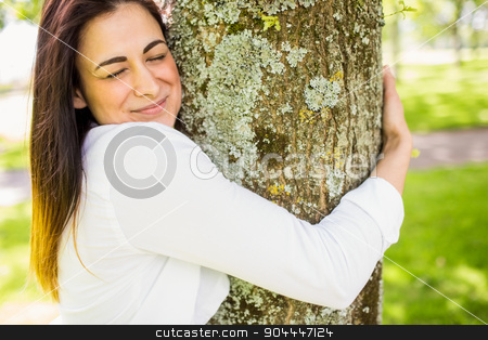 Beautiful brunette hugging a tree stock photo, Beautiful brunette hugging a tree on a sunny day by Wavebreak Media