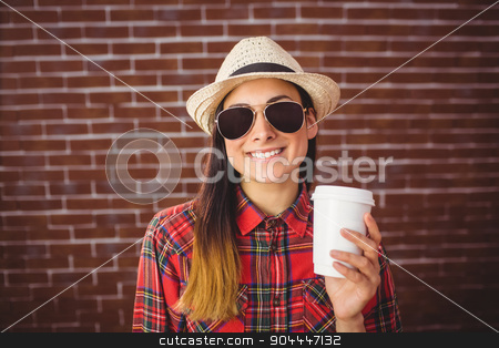 Beautiful hipster with disposable coffee stock photo, Beautiful hipster with disposable coffee on red brick background by Wavebreak Media