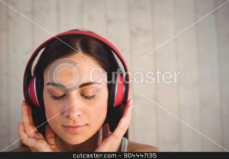 Pretty hipster listening to music stock photo, Pretty hipster listening to music on wooden planks background by Wavebreak Media