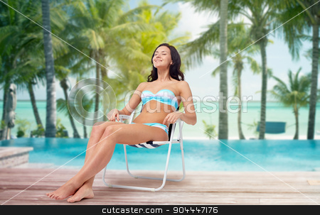happy young woman sunbathing in bikini on beach stock photo, people, tanning, summer and beach concept - happy young woman in bikini swimsuit sunbathing on folding chair over tropical beach with palm trees and pool at hotel resort background by Syda Productions