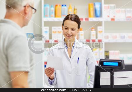 pharmacist reading prescription and senior man stock photo, medicine, pharmaceutics, health care and people concept - pharmacist reading prescription and senior man at drugstore cash register by Syda Productions