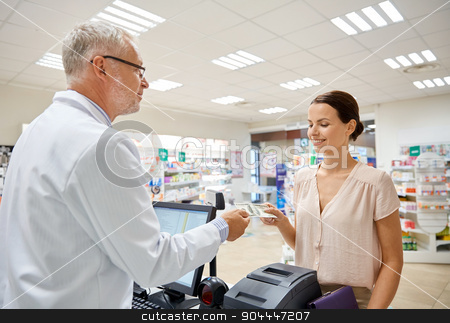 woman giving money to pharmacist at drugstore stock photo, medicine, pharmaceutics, health care and people concept - smiling woman with wallet giving money to senior man pharmacist at drugstore cash register by Syda Productions