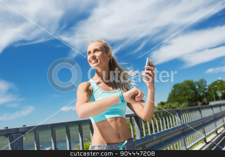 happy woman with heart rate watch and smartphone stock photo, fitness, sport, people, technology and healthy lifestyle concept - smiling young woman with heart rate watch and smartphone exercising outdoors by Syda Productions