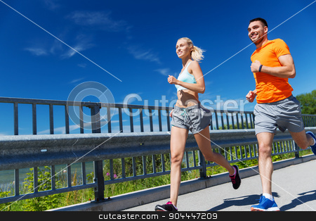 smiling couple running at summer seaside stock photo, fitness, sport, friendship and healthy lifestyle concept - smiling couple with heart-rate watch running at summer seaside by Syda Productions