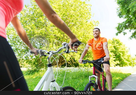 close up of happy couple riding bicycle outdoors stock photo, fitness, sport, people and healthy lifestyle concept - close up of happy couple riding bicycle outdoors at summer by Syda Productions