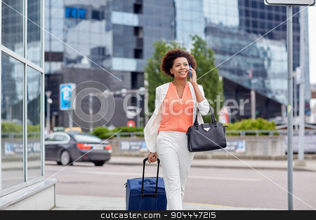 happy woman with travel bag calling on smartphone stock photo, travel, business trip, people and technology concept - happy young african american woman with travel bag walking down city street and calling on smartphone by Syda Productions