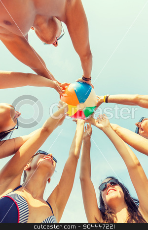 smiling friends in circle on summer beach stock photo, friendship, happiness, summer vacation, holidays and people concept - group of smiling friends wearing swimwear standing in circle with beach ball over blue sky by Syda Productions