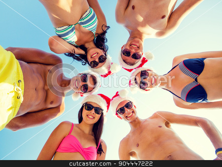 smiling friends in circle on summer beach stock photo, friendship, christmas, summer vacation, holidays and people concept - group of smiling friends wearing swimwear and santa helper hats standing in circle over blue sky by Syda Productions