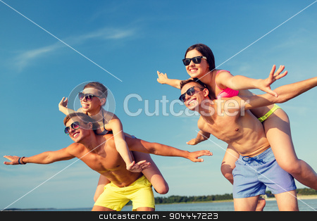 smiling friends having fun on summer beach stock photo, friendship, sea, summer vacation, holidays and people concept - group of smiling friends wearing swimwear and sunglasses having fun on beach by Syda Productions