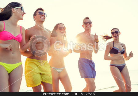 smiling friends in sunglasses running on beach stock photo, friendship, sea, summer vacation, holidays and people concept - group of smiling friends wearing swimwear and sunglasses running on beach by Syda Productions