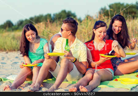 smiling friends sitting on summer beach stock photo, friendship, happiness, summer vacation, holidays and people concept - group of smiling friends having picnic on beach by Syda Productions