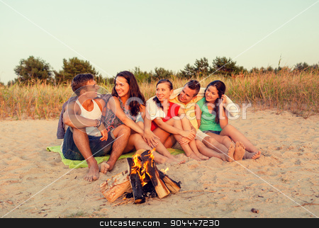 smiling friends in sunglasses on summer beach stock photo, friendship, happiness, summer vacation, holidays and people concept - group of smiling friends sitting near fire on beach by Syda Productions