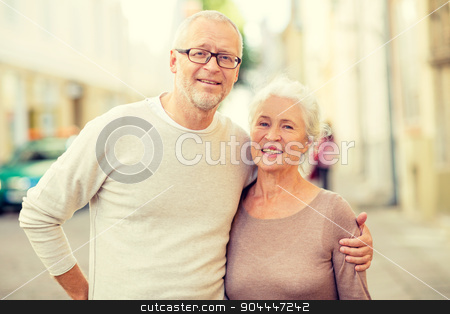 senior couple on city street stock photo, family, age, tourism, travel and people concept - senior couple hugging on city street by Syda Productions