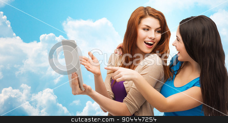 two smiling teenagers with tablet pc computer stock photo, technology, friendship and people concept - two smiling teenage girls or young women pointing finger at tablet pc computer over blue sky with clouds background by Syda Productions