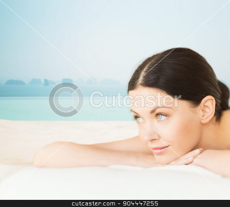 happy beautiful woman lying in spa stock photo, people, beauty and body care concept - happy beautiful woman lying on massage desk at spa resort over sea and infinity pool background by Syda Productions