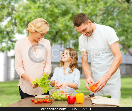 happy family cooking vegetable salad for dinner stock photo, vegetarian food, culinary, happiness and people concept - happy family cooking vegetable salad for dinner over over summer house background by Syda Productions